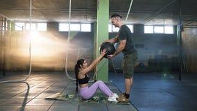 Pares hermosos del deporte que hacen que los ABS ejercitan con la bola de los aeróbicos con el hombre atractivo del deporte almacen de video