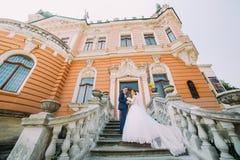Pares hermosos del recién casado en las escaleras en parque Palacio romántico del vintage en el fondo Foto de archivo