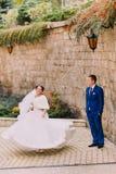 Pares hermosos elegantes de la boda, baile alegre de la novia para el novio cariñoso cerca de la pared de la piedra arenisca Imagen de archivo