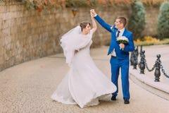 Pares hermosos elegantes de la boda, dando un paseo en parque cerca de la pared de la piedra arenisca Foto de archivo