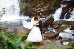 Pares hermosos elegantes de la boda que presentan cerca de la cascada magnífica hermosa en montaña Vestido de boda lujoso Los par foto de archivo