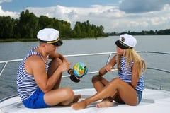 Pares hermosos elegantes que se sientan en un barco con Fotos de archivo libres de regalías