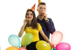 Pares hermosos en amor con los conos en sus cabezas que llevan los globos y los cuernos del soplo aislados en un fondo blanco Imagen de archivo libre de regalías