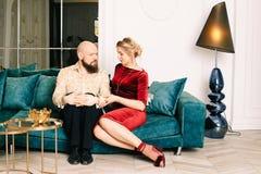 Pares hermosos en el amor que se sienta en el sof? foto de archivo libre de regalías