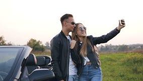 Pares hermosos en el amor que toma el selfie que se coloca cerca del coche cabriolet metrajes
