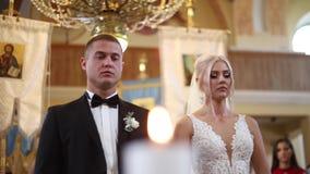 Pares hermosos en iglesia Los recienes casados juran el uno al otro para amar para siempre Novia y novio felices almacen de metraje de vídeo