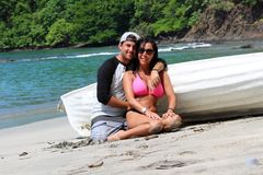 Pares hermosos en la playa con un barco, una mujer atractiva magnífica de las expresiones felices y un individuo latino en Costa  foto de archivo libre de regalías