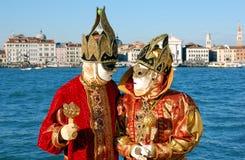 Pares hermosos en trajes coloridos y máscaras, opinión sobre la plaza San Marco Foto de archivo libre de regalías