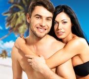 Pares hermosos felices en amor en la playa tropical Imágenes de archivo libres de regalías