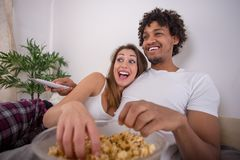 Pares hermosos felices que comen las palomitas mientras que ve la TV en cama fotos de archivo