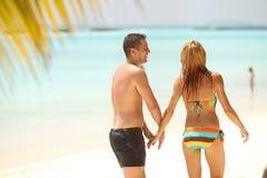 Pares hermosos felices que gozan en la playa en el día soleado h de Maldivas Foto de archivo libre de regalías