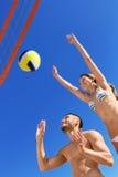 Pares hermosos felices que juegan a voleibol Imagenes de archivo