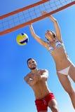 Pares hermosos felices que juegan a voleibol foto de archivo