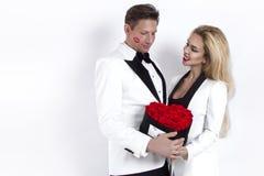 Pares hermosos felices que presentan en el fondo blanco y que sostienen la caja de la flor con el corazón rojo Día del ` s de la  imagen de archivo