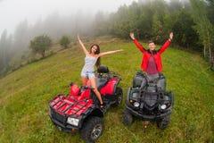 Pares hermosos felices que se sientan en los coches de cuatro ruedas ATV Foto de archivo libre de regalías