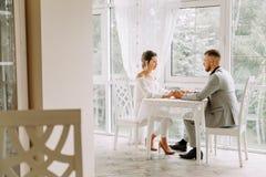 Pares hermosos felices que se sientan en un restaurante y hablar Imagen de archivo libre de regalías