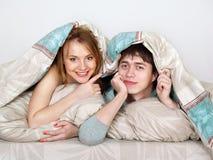 Pares hermosos jovenes bajo lanket en una cama imagenes de archivo