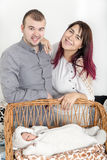 Pares hermosos jovenes con el nuevo bebé en casa Imagen de archivo