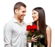 Pares hermosos jovenes con las flores aisladas en blanco Fotos de archivo libres de regalías