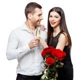 Pares hermosos jovenes con las flores aisladas en blanco Fotografía de archivo