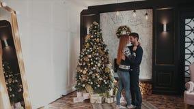 Pares hermosos jovenes en el amor huging en el fondo del árbol de navidad almacen de metraje de vídeo