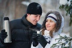 Pares hermosos jovenes en parque del invierno. Imagen de archivo