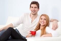 Pares hermosos jovenes en un sofá en casa imagenes de archivo