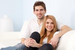 Pares hermosos jovenes en un sofá en casa fotografía de archivo