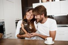 Pares hermosos jovenes felices que se sientan en la cocina que celebra la sonrisa del gato Fotos de archivo