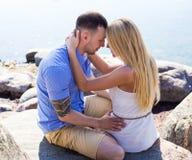 Pares hermosos jovenes felices que se sientan en la playa rocosa Foto de archivo libre de regalías