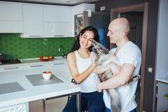 Pares hermosos jovenes felices que se sientan en la sonrisa del gato de la cocina Imagen de archivo libre de regalías