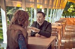 Pares hermosos jovenes lindos que se sientan en el restaurante Imagen de archivo