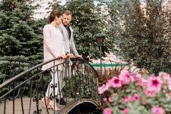 Pares hermosos jovenes que caminan en el parque y los soportes en el puente Imagen de archivo