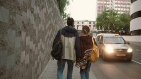 Pares hermosos jovenes que caminan en la ciudad por la tarde Estudiantes, hombre y mujer con la mochila que va cerca del camino d almacen de video