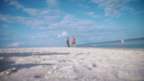Pares hermosos jovenes que caminan a lo largo de la costa en un día soleado defocus Abundancia de azul almacen de metraje de vídeo