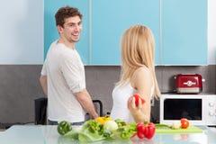Pares hermosos jovenes que cocinan en casa Fotos de archivo libres de regalías