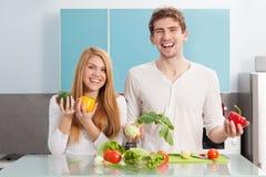 Pares hermosos jovenes que cocinan en casa fotografía de archivo