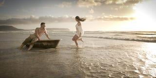 Pares hermosos jovenes que disfrutan de una tarde en la playa fotos de archivo