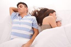 Pares hermosos jovenes que duermen junto en cama Foto de archivo libre de regalías