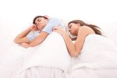 Pares hermosos jovenes que duermen junto en cama Imagenes de archivo