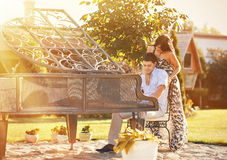 Pares hermosos jovenes que juegan en un piano en un parque Fotos de archivo libres de regalías