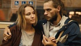 Pares hermosos jovenes que llevan a cabo las manos y que hablan en coche de subterráneo El tren para y el hombre y la mujer del i almacen de video