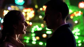 Pares hermosos jovenes que pasan el tiempo junto el fecha en parque de atracciones en la noche Estación del otoño Mirada de los a metrajes