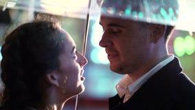 Pares hermosos jovenes que pasan el tiempo junto el fecha en parque de atracciones en la noche Tiempo lluvioso, otoño Colocación  almacen de metraje de vídeo