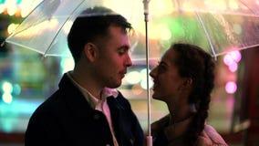 Pares hermosos jovenes que pasan el tiempo junto el fecha en parque de atracciones en la noche Tiempo lluvioso, otoño Colocación  metrajes