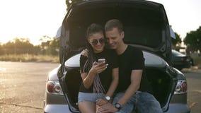 Pares hermosos, jovenes que pasan el tiempo junto Sentándose en tronco de coche abierto, abrazando y mirando al smarphone ambos almacen de video
