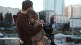 Pares hermosos jovenes que se colocan en el centro y el abrazo de ciudad Hombre y mujer felices una fecha romántica metrajes