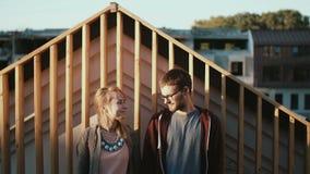 Pares hermosos jovenes que se colocan en el tejado y que disfrutan de la opinión escénica sobre puesta del sol Fecha romántica de almacen de video