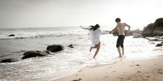 Pares hermosos jovenes que se divierten que salta a lo largo de la playa Imágenes de archivo libres de regalías