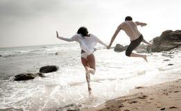 Pares hermosos jovenes que se divierten que salta a lo largo de la playa fotos de archivo libres de regalías